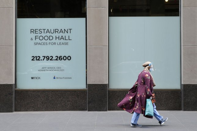 A CDC analysis has traced many of the COVID-19 cases there to virus strains found in Europe. Pictured, a woman wears a face mask and shield while walking by a space for lease sign in Rockefeller Center in New York City. Photo by John Angelillo/UPI
