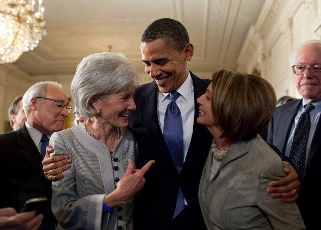 U.S. President Barack Obama embraces Secretary of Health and Human Services Kathleen Sebelius (L) and House Speaker Nancy Pelosi (D-CA) after signing the health insurance reform bill in the East Room of the White House, March 23, 2010. UPI/Pete Souza/The White House