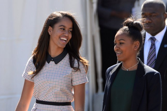 Malia (L) and Sasha Obama walk to their seats before their father, President Barack Obama said the family will remain in Washington, D.C., after he leaves the White House so Sasha can complete high school at Sidwell Friends School. Photo by David Tulis/UPI