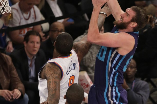 Charlotte Hornets forward Spencer Hawes (00) leaps to grab a rebound over New York Knicks forward Kyle O'Quinn (9) and center Kevin Seraphin (1) in the second quarter at Madison Square Garden in New York City on April 6, 2016. Photo by Ray Stubblebine/UPI