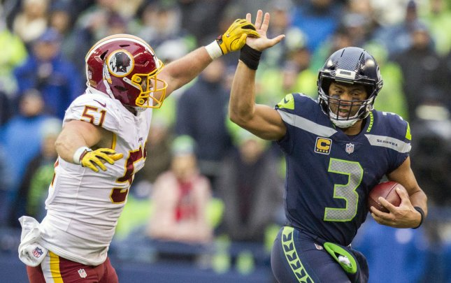 Seattle Seahawks quarterback Russell Wilson fends off an attempted tackle by Washington Redskins linebacker Will Compton during their game Sunday. The Seahawks face the Arizona Cardinals on Thursday night. Photo by Jim Bryant/UPI