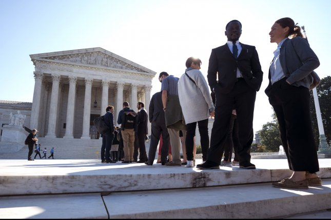 Members of public gather outside of the U.S. Supreme Court Monday on the first day of its new term