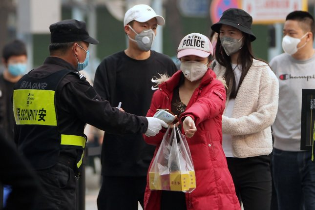 People in Beijing wear protective face masks and have their temperature checked by security at a fashion galleria on Thursday. Photo by Stephen Shaver/UPI