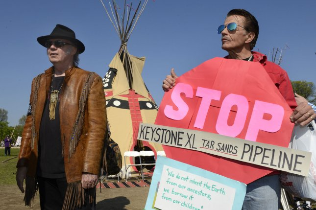 Rock star Neil Young (L) arrives to meet protestor Ron Raz of Pipersville, Pennsylvania as they prepare to join marchers during a demonstration organized by the Cowboy Indian Coalition (CIA) to protest against the building of the Keystone XL pipeline, April 26, 2014, in Washington, DC. Ranchers, farmers, Native Americans and environmentalists are calling on President Obama to reject the pipeline. UPI/Mike Theiler