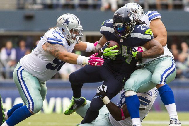 Former Seattle Seahawks running back Marshawn Lynch (24) is gang tackled by former Dallas Cowboys defensive tackle Nick Hayden (96) and defensive ends Tyrone Crawford (98). UPI/Jim Bryant