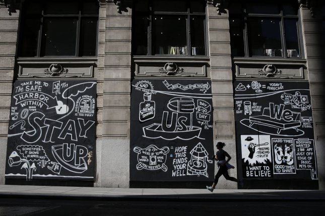 A woman jogs by graffiti sprayed on boarded windows at Manhattan's closed Aritzia Fashion Boutique retail store, on June 22 in the SOHO neighborhood of New York City. Photo by John Angelillo/UPI
