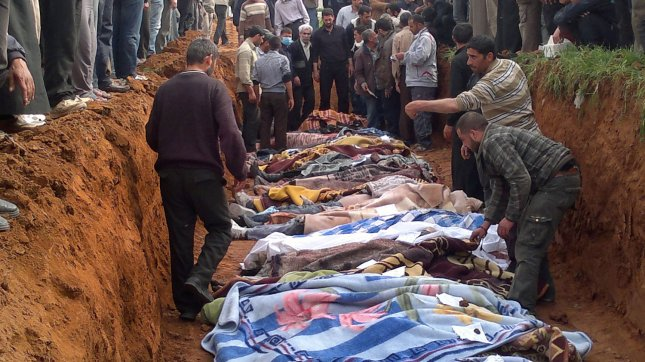 People bury the bodies of men activists say were killed by the Syrian government army, in Taftanaz village, east of Idlib, Syria April 5, 2012. UPI