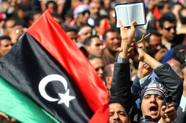 A protester holds the Koran, Islam's holy book,at Cairo's Tahrir Square on March 11, 2011 as hundreds of Egyptians demonstrated against sectarianism, following religious clashes that left at least 13 people dead. The flag is a former Libyan national flag. UPI/Mohammed Hosam