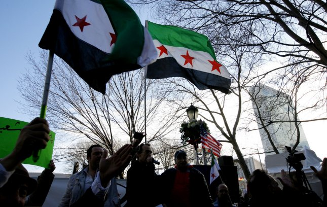 Syrian flags are waved as demonstrators gather before the start of the Security Council meeting where U.S. Secretary of State Hillary Clinton will ask members to support of an Arab League peace plan for Syria at the United Nations on January 31, 2012 in New York City. The proposed plan calls for the transfer of power from Syrian President Bashar al-Assad to his deputy and for free elections to be held. UPI/Monika Graff