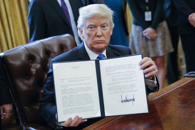 U.S. President Donald Trump displays one of five executive orders he signed Tuesday related to the oil pipeline industry in the Oval Office of the White House in Washington, D.C. Pool photo by Shawn Thew/UPI
