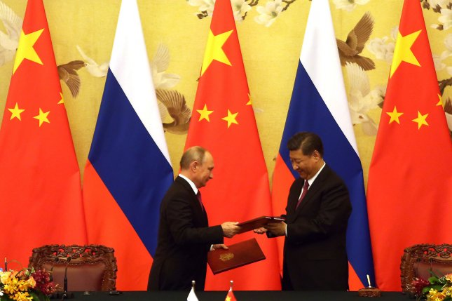 Russian President Vladimir Putin (L) and Chinese President Xi Jinping exchange trade agreements at a signing ceremony in Beijing on June 8. File Photo by Stephen Shaver/UPI