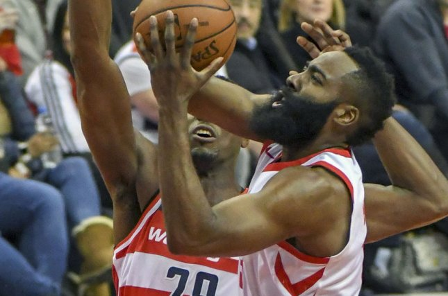Houston Rockets guard James Harden (13) scores against Washington Wizards center Ian Mahinmi (28) in the first half on December 29 at Capital One Arena in Washington, D.C. Photo by Mark Goldman/UPI