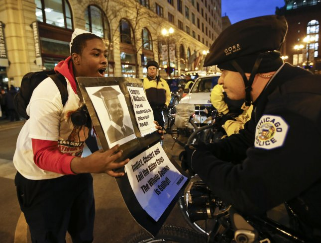 Dantreal Widow, left, confronts a Chicago Police Officer while protesting the 2014 police shooting of Laquan McDonald in Chicago on November 25, 2015. The 17-year old Laquand, who was armed with a small knife fleeing police, was shot 16 times by an officer on the night of October 20, 2014. File Photo by Kamil Krzaczynski/UPI
