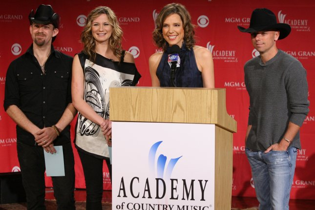From left to right, Kristian Bush and Jennifer Nettles of the band Sugarland, pose with reporter Hannah Storm and country music singer Kenny Chesney at the 42nd Annual Academy of Country Music Awards on March 5, 2007 at the Country Music Hall of Fame in Nashville, Tennessee. File photo by Frederick Breedon IV/UPI