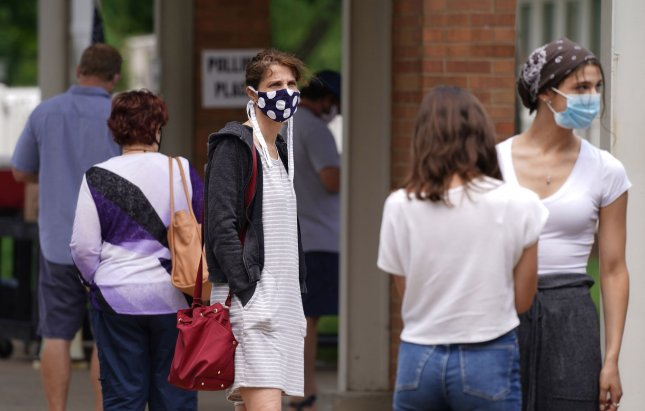 Voters, wearing masks and distancing themselves while standing in line, wait Tuesday for the chance to vote in the Missouri primary in Olivette, Mo. Photo by Bill Greenblatt/UPI
