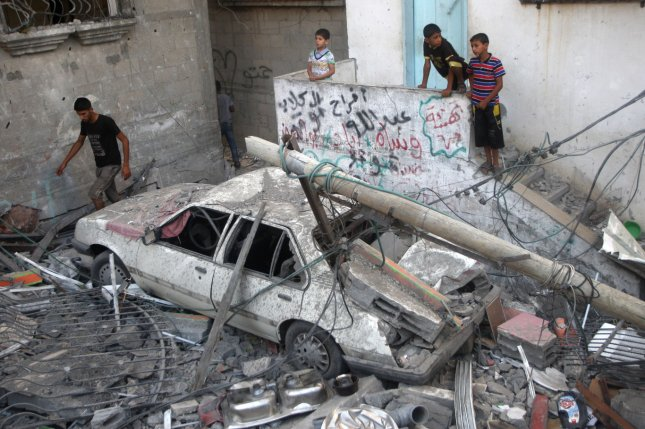 Palestinians looks at the rubble of a building destroyed following an Israeli military strike in Rafah in the south of the Gaza Strip on August 21, 2014. The armed wing of Hamas announced that three of its senior commanders were killed in a pre-dawn Israeli air strike in southern Gaza. UPI/Ismael Mohamad