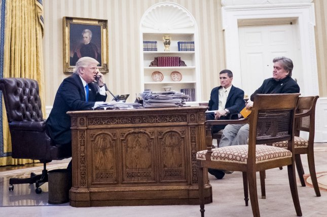Former national security advisor Michael Flynn (C) and senior counselor to the president Steve Bannon sit nearby as President Donald Trump speaks on the phone with Prime Minister of Australia, Malcolm Turnbull, in the Oval Office on January 28. High-ranking aides to Trump, including Flynn and Bannon, may have been in contact with known Russian agents during and after the presidential election, intelligence and government officials said late Tuesday night. Photo by Pete Marovich/UPI