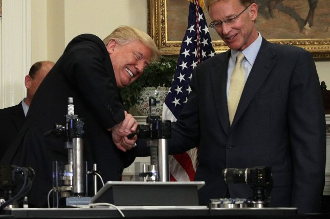 U.S. President Donald Trump (L) tries to break a medicine vial with a vise as Corning CEO Wendell Weeks (R) looks on during an announcement regarding a pharmaceutical glass packaging initiative Thursday in Washington, D.C. Pool Photo by Alex Wong/UPI