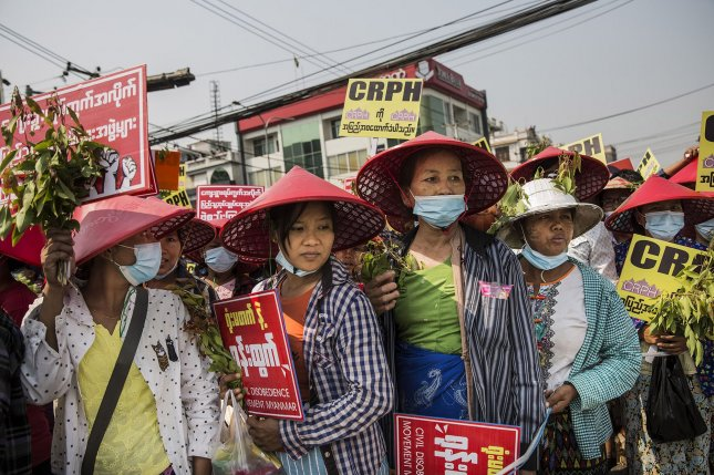 Burmese protesters carry signs during a demonstration against the military coup in Mandalay, Myanmar, Sunday, February. 28. Photo by Xiao Long/UPI