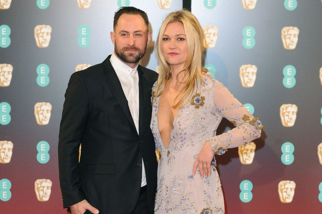 Julia Stiles (R) and Preston J. Cook attend the EE British Academy Film Awards on February 12. The actress' rep confirmed Monday that Stiles is expecting her first child with Cook. File Photo by Paul Treadway/UPI