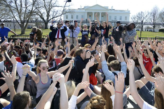 Students raise their hands during a moment of silence in front of the White House against gun violence in schools on Wednesday. Colleges across the nation said the demonstrations and even suspensions won't affect their admission prospects or result in acceptance revocation. Photo by Mike Theiler/UPI