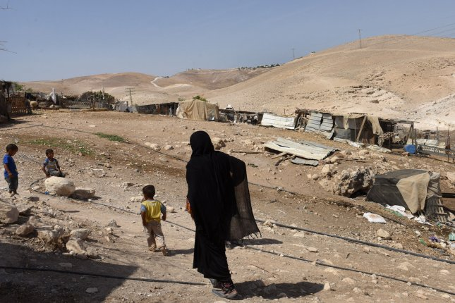Bedouins walk through a village in the Judean Desert in the West Bank, near the Kfar Adumim Jewish Settlement. Experts say more than 200 Palestinians have been displaced by Israeli plans to demolish their settlements. File Photo by Debbie Hill/UPI