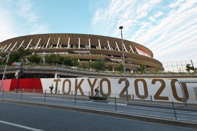 Pedestrians are seen on Monday walking outside National Stadium in Tokyo, Japan. The Tokyo Olympics begin on July 23. Photo by Keizo Mori/UPI