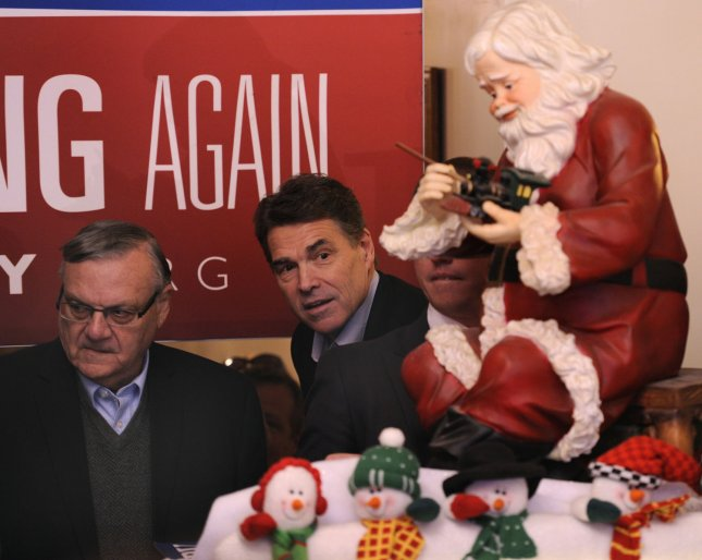 Republican 2012 presidential candidate and Texas Gov. Rick Perry looks from behind a Santa Claus along with Maricopa County (Arizona) Sheriff Joe Arpaio (L), as he arrives at Main Street Cafe, for a meet-and-greet of supporters, in Council Bluffs, Iowa, Dec. 27, 2011, in advance of Iowa's first-in-the-nation caucuses, Jan. 3,2012. UPI/Mike Theiler