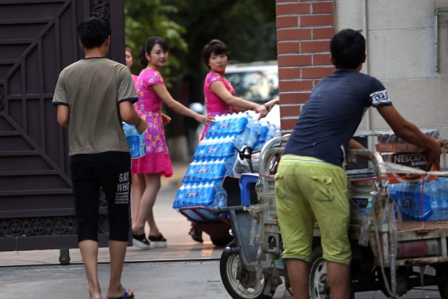 North Korean women pickup a delivery of beverages from Chinese men at their embassy in Beijing. A Japanese scholar who has visited North Korea nearly 50 times is piecing together clues about the country through his collection of North Korean garbage. Photo by Stephen Shaver/UPI