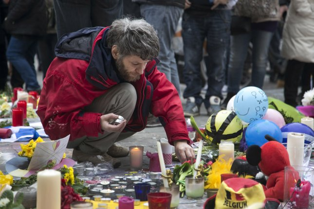 People gather to observe a minute of silence leave tributes to mourn the victims of the bombings at the Place de la Bourse in the center of Brussels, Belgium, on March 24, two days after a bomb attack, claimed by the Islamic State group. Photo by Albert Masias/UPI