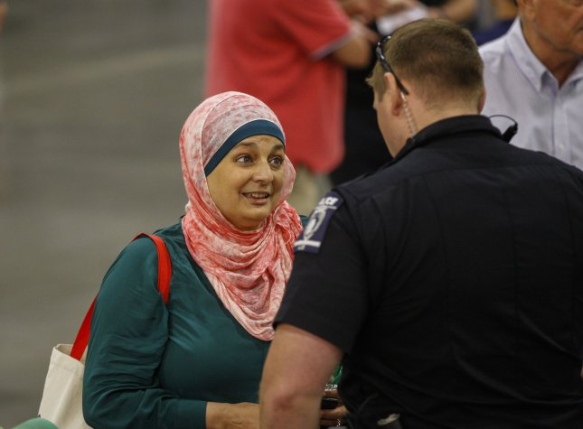 Rose Hamid, a Muslim woman, talks to a police officer as she is removed from a rally for U.S. Republican presidential candidate Donald Trump in Charlotte, N.C., on August 18. File Photo by Nell Redmond/UPI