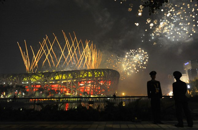 Fireworks explode over Beijing's National Stadium during the closing ceremonies at the Summer Olympics Aug. 24, 2008. The two viewers in the lower right corner are Chinese police officers. (UPI Photo/Mike Theiler)