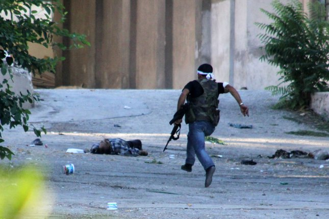 A member of the Free Syrian Army runs for cover against Syrian military positions in Aleppo, Syria, on Sept. 8, 2012. The Syrian Observatory for Human Rights on Dec. 1, 2015, reported more than 4,000 people were killed across Syria in November 2015. File photo by Ahmad Deeb/ UPI