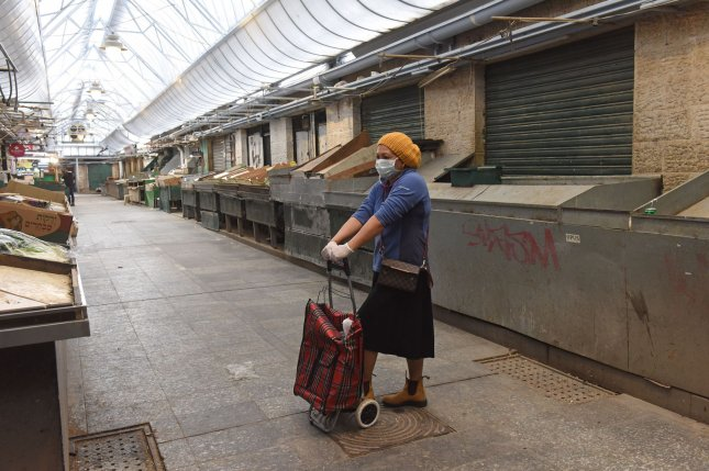 A woman wears a protective mask and gloves while standing in the shuttered Mahane Yehuda Market in Jerusalem on March 27. File Photo by Debbie Hill/UPI