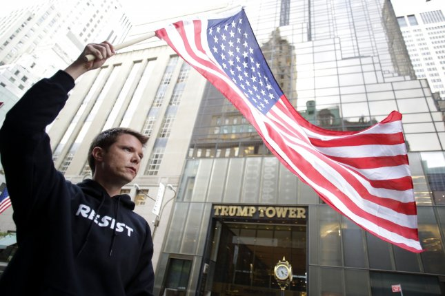 A protester holds an an American flag in front of Trump Tower on Fifth Avenue in New York City. Wednesday's ruling was the second in three months that went against Trump concerning access to prior tax returns. File Photo by John Angelillo/UPI