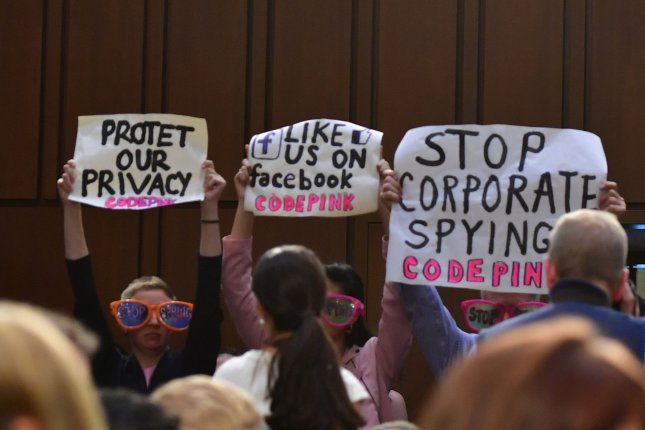 Demonstrators protest Tuesday as Facebook CEO Mark Zuckerberg testifies at a joint hearing before the Senate judiciary and commerce committees. Photo by Kevin Dietsch/UPI