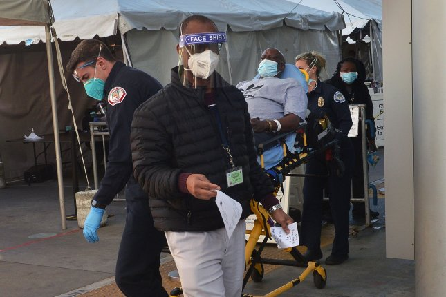 Emergency personnel lead a patient to a waiting ambulance at Martin Luther King Hospital in Los Angeles, Calif., on Wednesday. Photo by Jim Ruymen/UPI