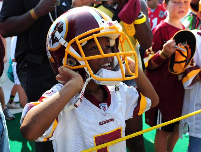 Ladaveon Butler, 7, of Washington, puts on one of the Washington Redskins player's helmets after the Redskins last day of training camp at Redskins Park in Ashburn, Va., Aug. 19, 2010. UPI/Kevin Dietsch