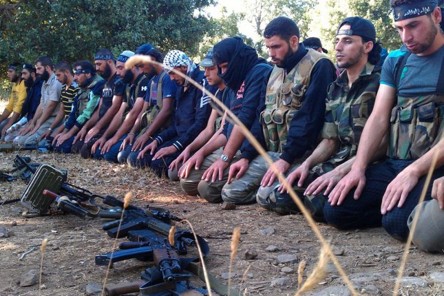 Members of the Free Syrian Army perform prayers in Damascus in August 13, 2012. Two years later, the rise of Islamist extremists are seizing territory controlled by the rebels as the civil war continues to rage. (UPI)