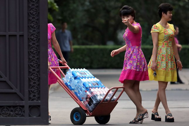 North Korean women pick up a delivery of beverages from Chinese men at their embassy in Beijing on August 26. There are now 26,514 defectors in South Korea, and a total of 28,607 North Koreans living outside their country of origin. File Photo by Stephen Shaver/UPI