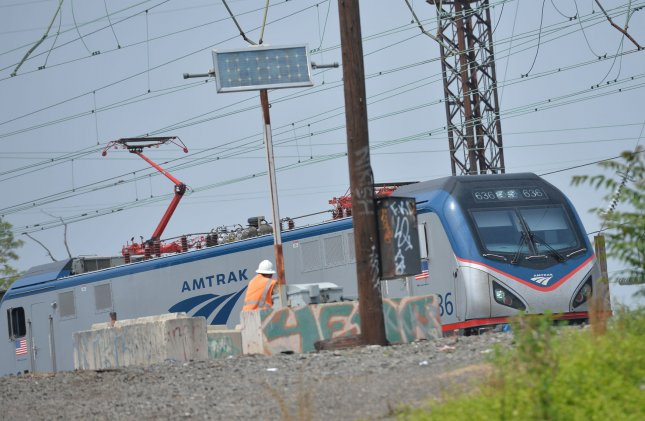 An Amtrak Acela train slowly passes a police car as it travels near Philadelphia on May 18, 2015. This week, unsealed court documents revealed a Missouri man with white supremacist links was arrested after he attempted to hijack an Amtrak train. File Photo by Kevin Dietsch/UPI