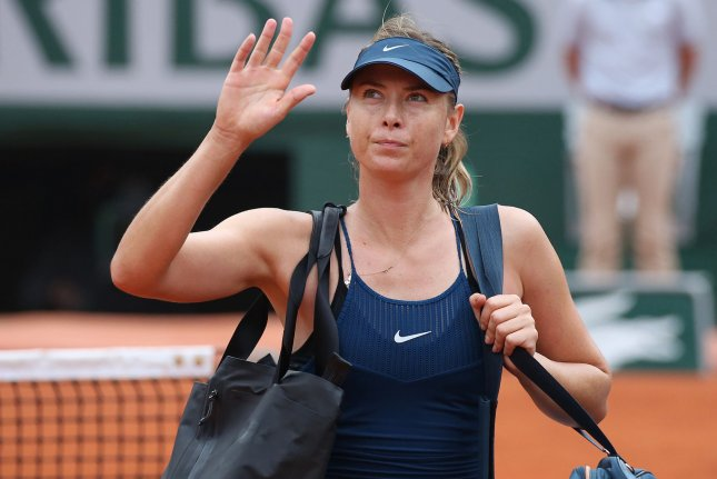 Maria Sharapova of Russia waves to the crowd after losing her French Open women's quarterfinal match against Garbine Muguruza of Spain Wednesday at Roland Garros in Paris. Photo by David Silpa/UPI