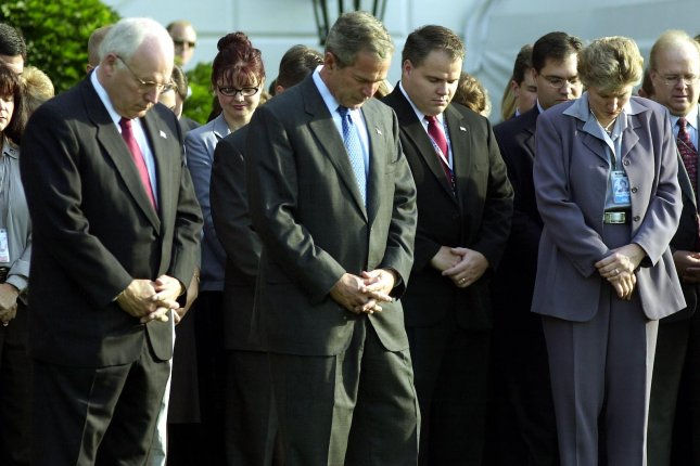 President George W. Bush leads his staff in a moment of silence on the south lawn of the White House in Washington, D.C., on September 18, 2001, with Vice President Dick Cheney to his left and advisor Karen Hughes to his right. File Photo by Michael Kleinfeld/UPI