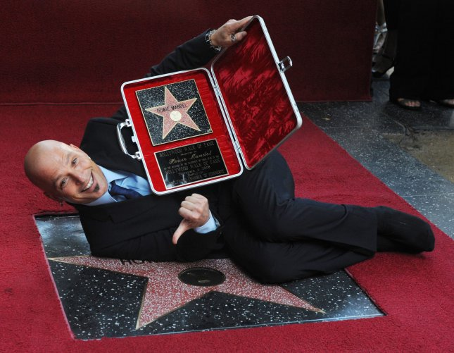 Canadian comedian Howie Mandel, the host of the TV game show Deal or No Deal, holds a replica plaque presented to him in a briefcase as he lies atop his star in stocking feet, after receiving the 2,368th star during an unveiling ceremony on the Hollywood Walk of Fame in Los Angeles on September 4, 2008. (UPI Photo/Jim Ruymen)