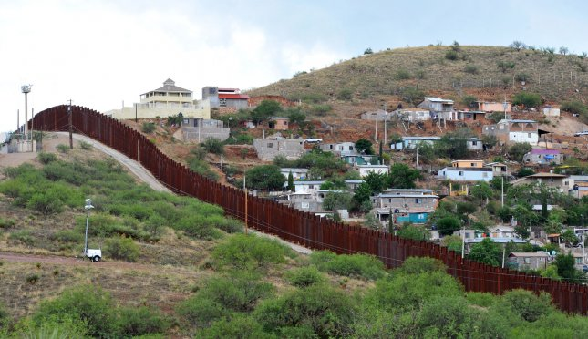 The border fence stretches for miles between the United States and Mexico near Nogales, Arizona on July 13, 2014. More than 57,000 children from Central America have crossed the U.S. border alone since October 1, 2013. President Obama has asked congress for $3.7 million to deal with the influx. UPI/Art Foxall