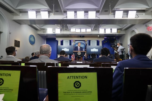 President Donald Trump speaks to reporters during a briefing Wednesday at the White House in Washington, D.C. Warning signs posted to chairs in the briefing room caution journalists to observe measures to mitigate the spread of COVID-19. Photo by Chris Kleponis/UPI