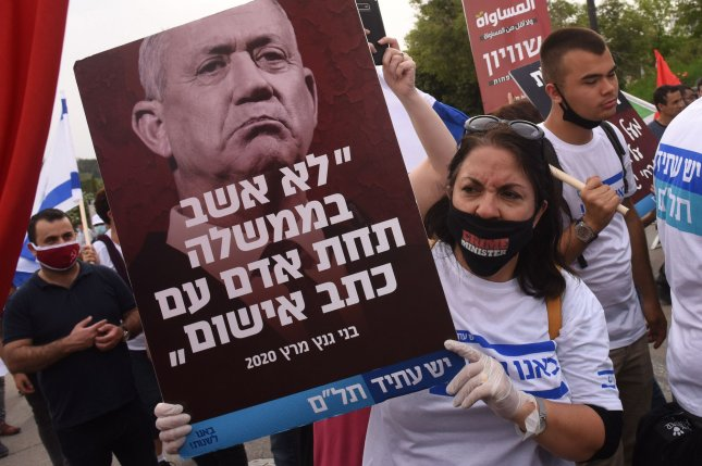 A woman wears a protective mask and holds a sign during a demonstration against Prime Minister Benjamin Netanyahu's new unity government with rival Benny Gantz outside the Knesset in Jerusalem on Thursday. Photo by Debbie Hill/UPI