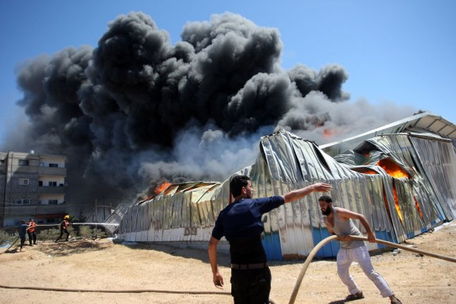 People and members of the Palestinian Civil Defense extinguish a fire in a paint warehouse that was hit by an Israeli artillery shell on eastern Rafah, in the southern Gaza Strip, on Tuesday. Photo by Ismael Mohamad/UPI
