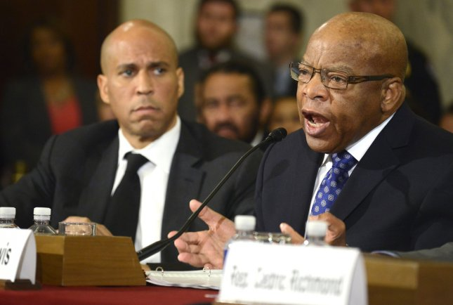 Rep. John Lewis (R) makes remarks as Sen. Cory Booker listens during Senate Judiciary Committee confirmation hearings for Attorney General nominee Jeff Sessions, on Capitol Hill, January 11, in Washington, DC. Lewis said he does not consider President-elect Donald Trump a legitimate president and announced he will not attend his inauguration during an interview with NBC News. Trump responded to Lewis' comments on Twitter by criticizing his work in Georgia's 5th congressional district. Photo by Mike Theiler/UPI