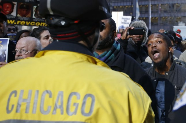 A demonstrator confronts a Chicago police officer while protesting the Chicago Police Department in the wake of a series of videos showing possible misconduct and videos of officer Jason Van Dyke's shooting of 17-year-old Laquan MacDonald. The McDonald case is one of several deadly police shootings over the last year that prompted two Democratic congressmen to introduce legislation in 2015 encouraging states to use independent investigators in cases of deadly officer-involved shootings to avoid possible conflicts of interest. Photo by Kamil Krzaczynski/UPI